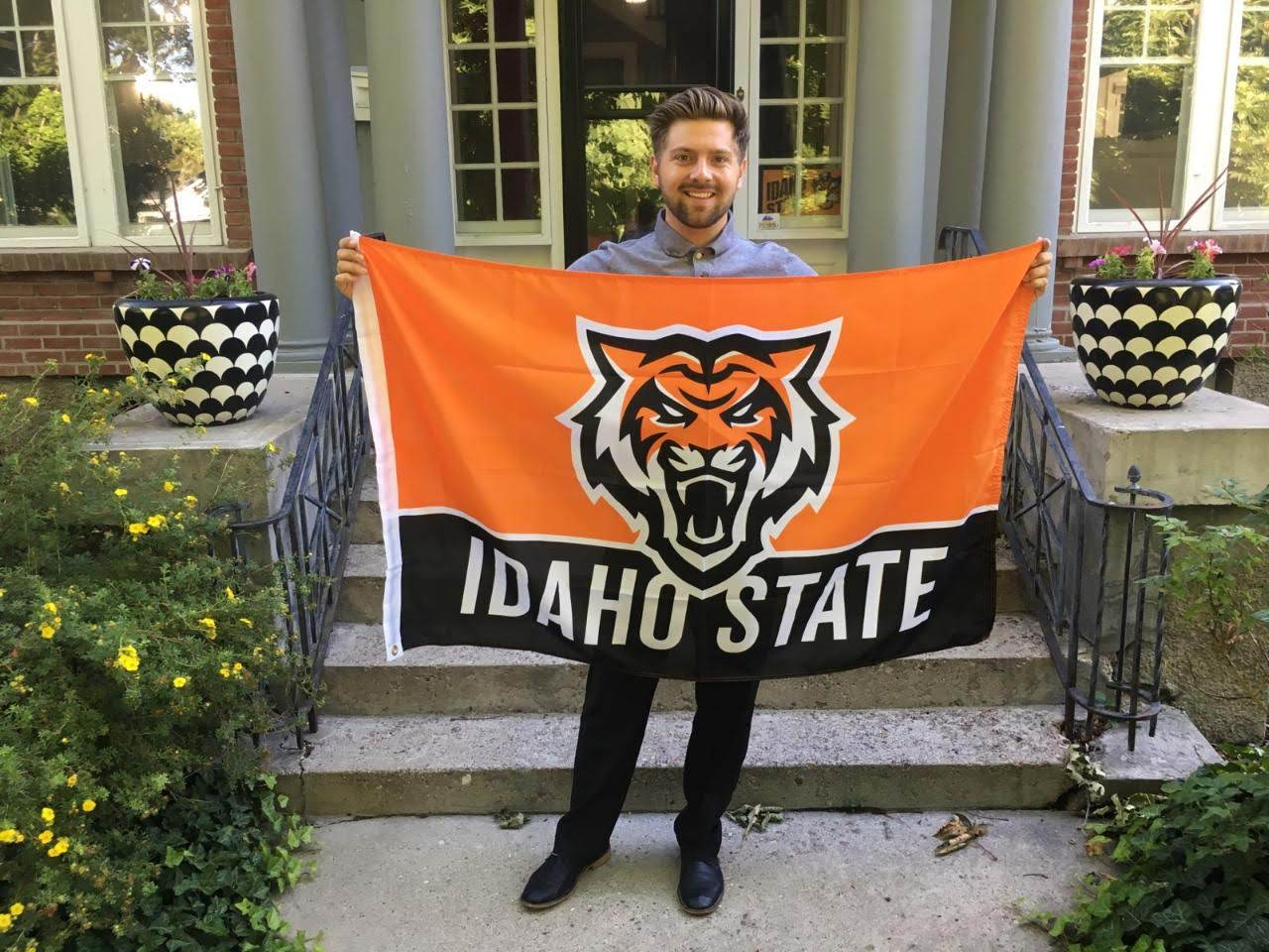 Employee holding new branding Idaho State Flag with Bengal Head