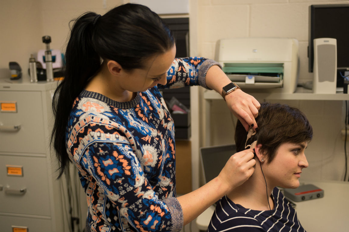 Audiologist placing a hearing aid