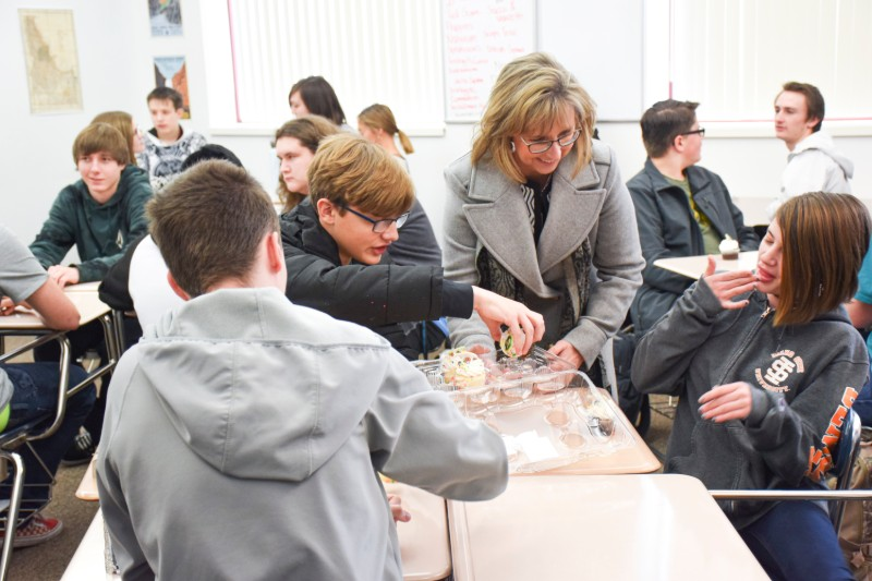 Dean Kandi Turley-Ames hands cupcakes to high school students.