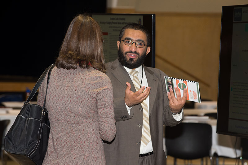 Student explaining research at the graduate research symposium