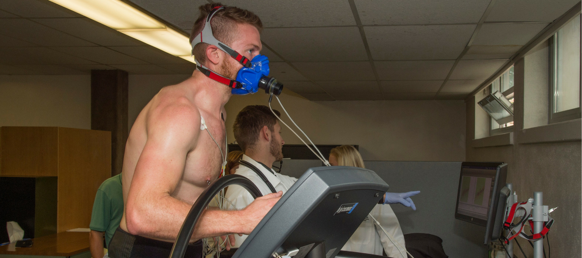 College aged male running on treadmill with an oxygen mask attached to his face