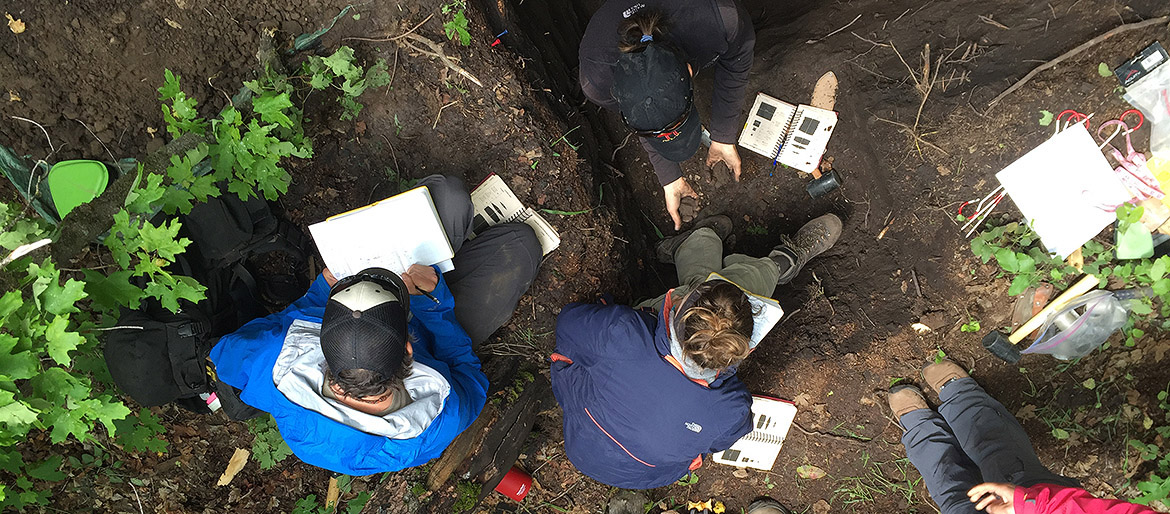 Students in pit gathering soil information