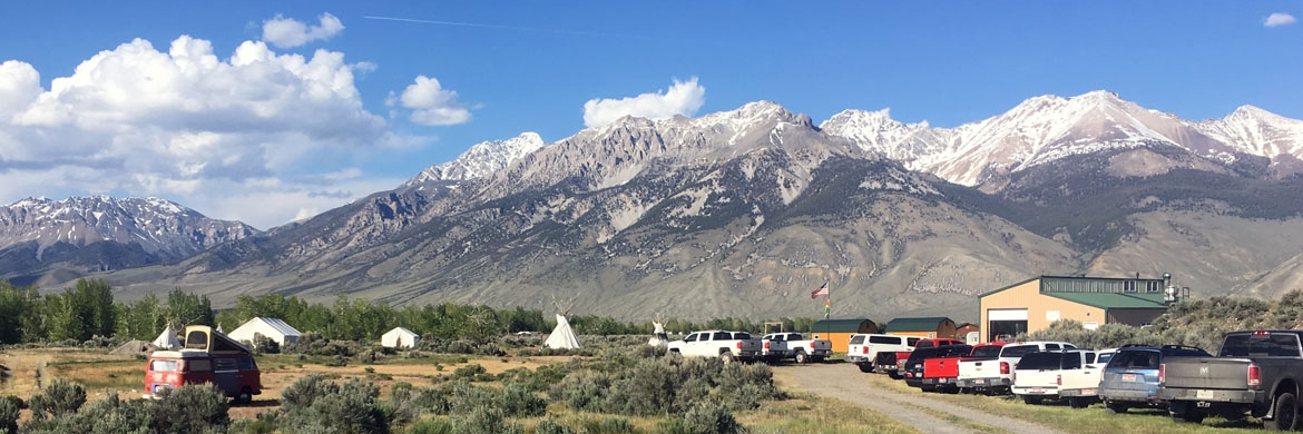 Field camp with cars in the foreground and mountains in the background
