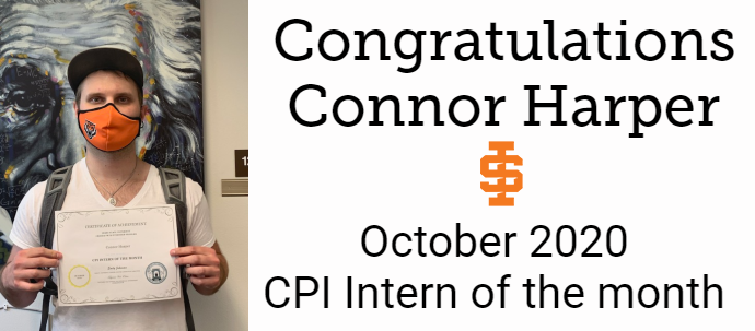 Connor Harper wearing a mask and holding up his October 2020 CPI Student of the Month certificate with