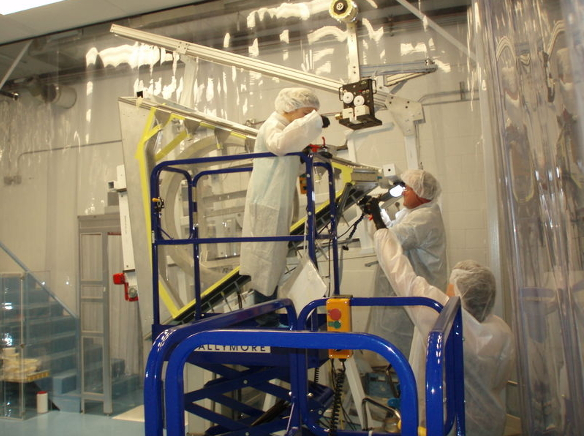 People in lab coats working on some equipment