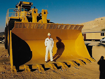John Koehne Instruction Assistant, Automotive Collision Repair and Refinishing Standing on a Caterpillar 240 ton truck