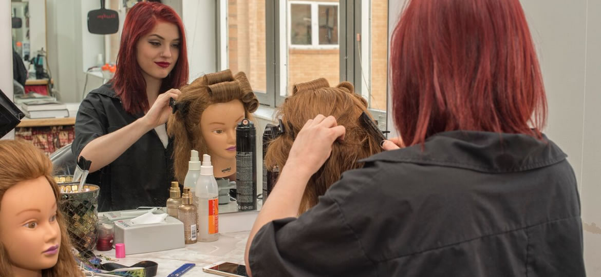 Cosmetology student practicing on a mannequin