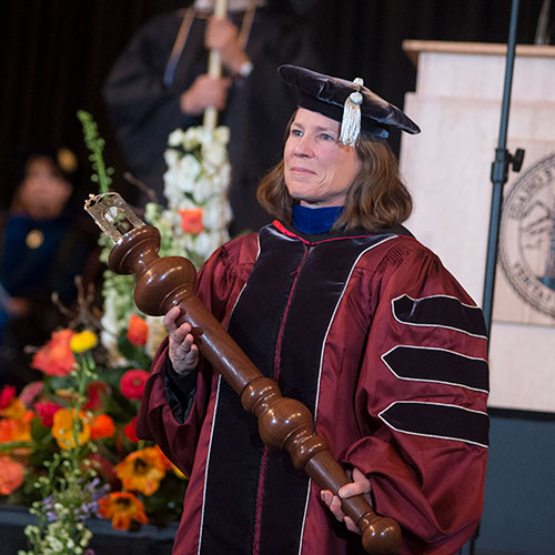 Professor presenting the Mace during ceremony