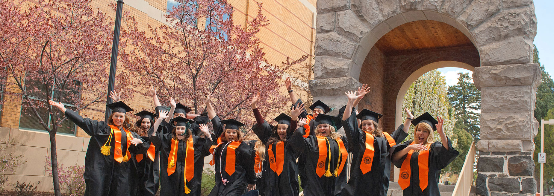 Graduates cheering at Swanson Arch