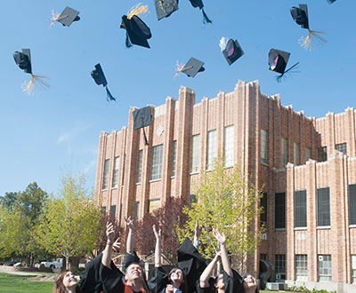Graduates throwing mortar board into the air