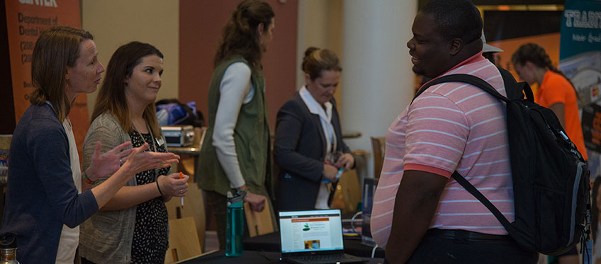 Counseling center employees talk to students at a health fair