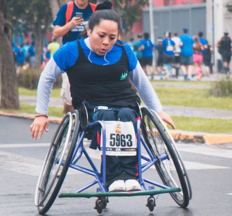 Female dietitian coming across finish line of wheelchair road race