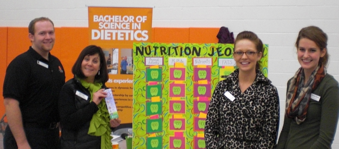 One male, three female students at community health fair, playing Nutrition Jeopardy