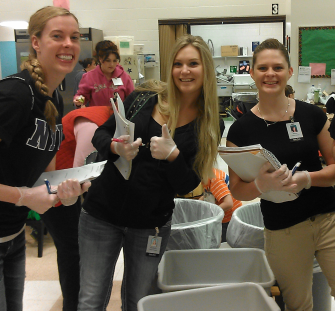 One male and three female dietetic interns conduct plate waste study at local grade school