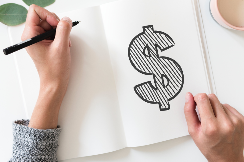 Woman writing in notebook, opened to page with large dollar sign