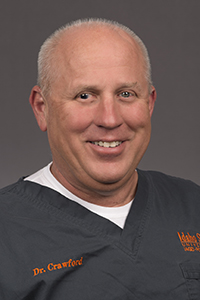 Brian Crawford, DDS, in gray and orange ISU scrubs