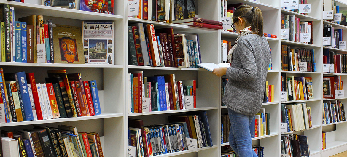 Woman perusing books in a library