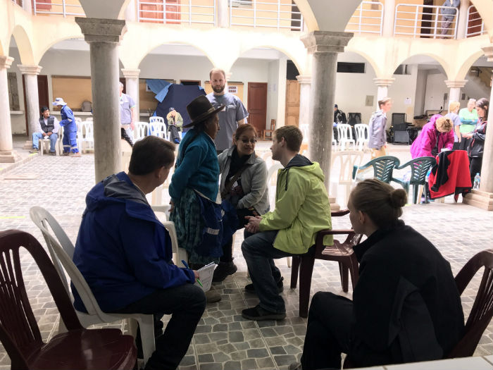 Physician treating patients in Peru in an outdoor clinic