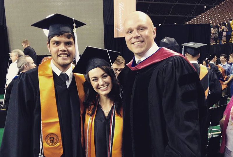 students and professor at graduation