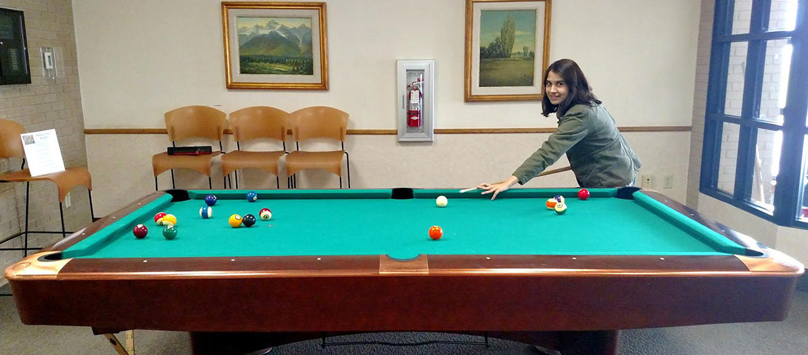 Student plays pool in the recreation room