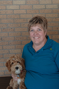 Tania Harden with Flin, a goldendoodle, in front a brick wall