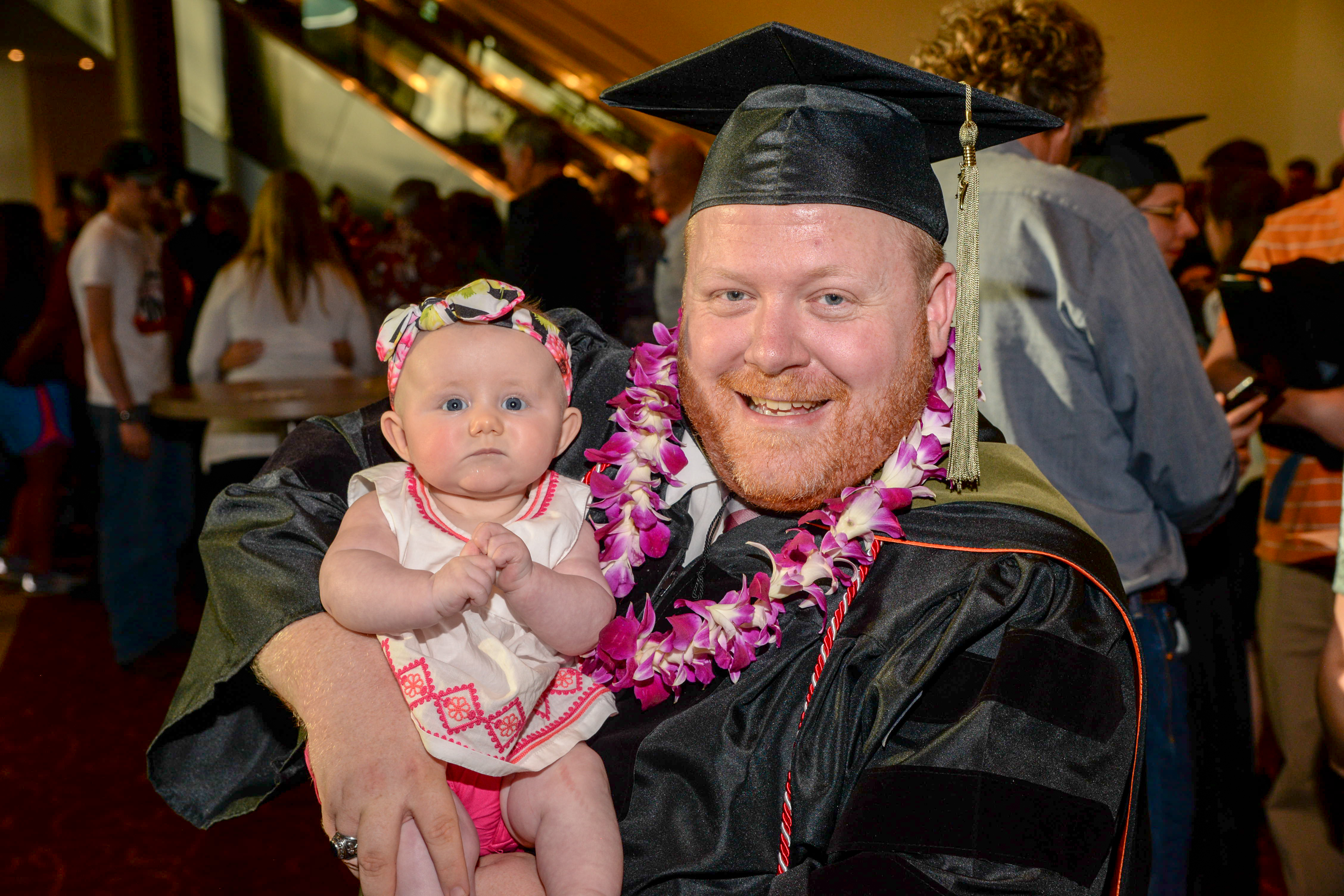 Smiling male graduate waring his gown and a lei holding a baby girl.
