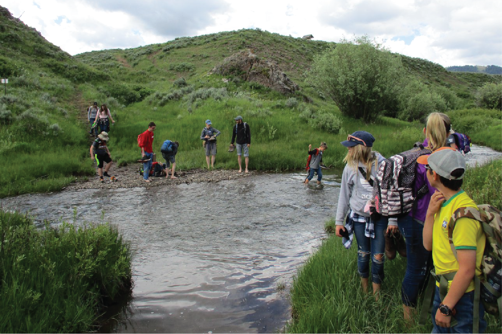 Group of kids crossing a stream on a field trip