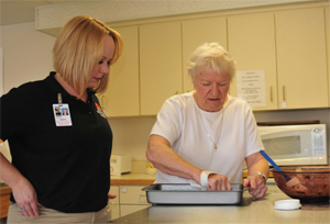 An occupational therapist baking a dish with a patient