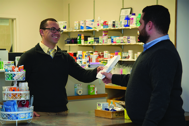 Pharmacist hands prescriptions to patient
