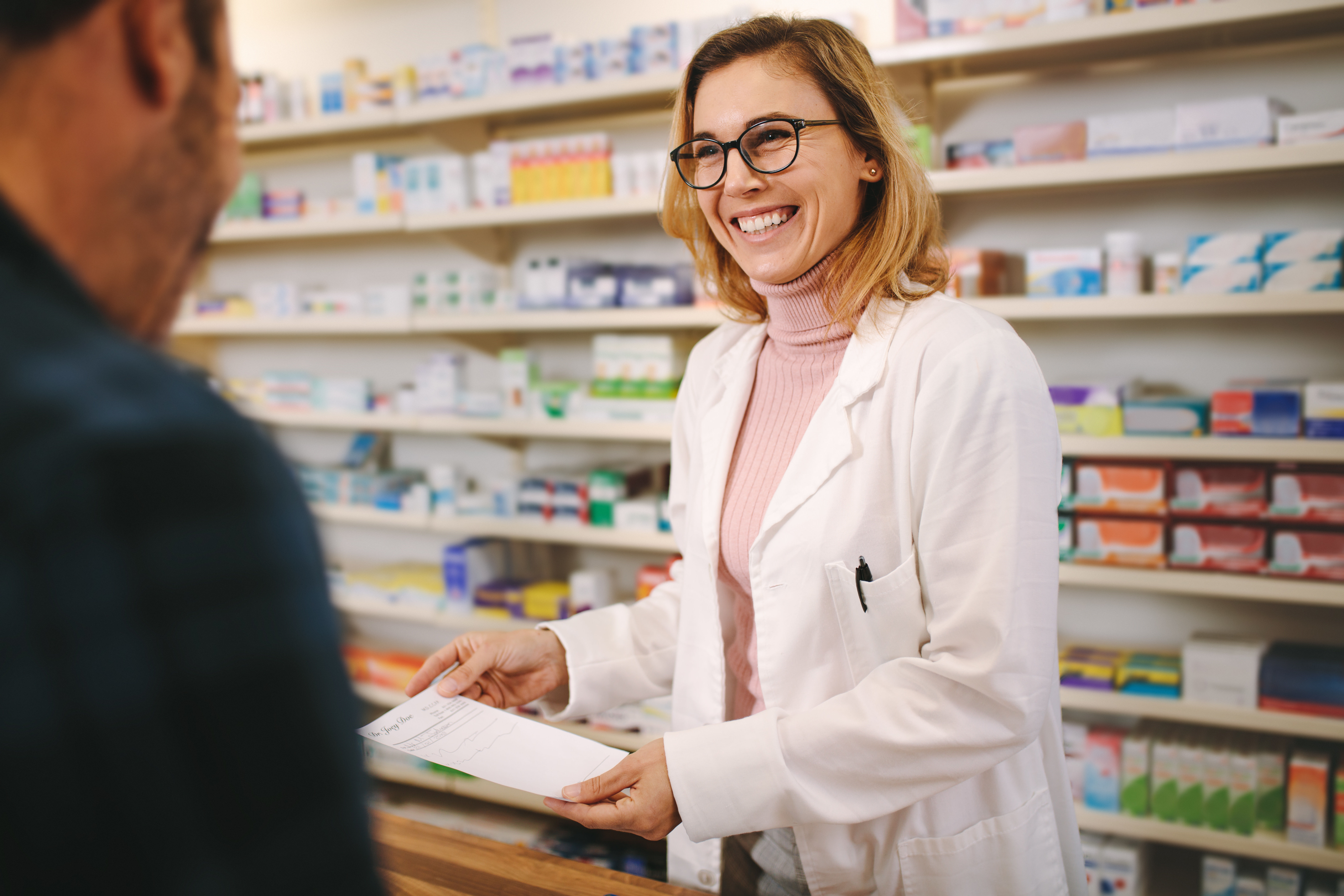 Pharmacist smiling at patient who is receiving a prescription