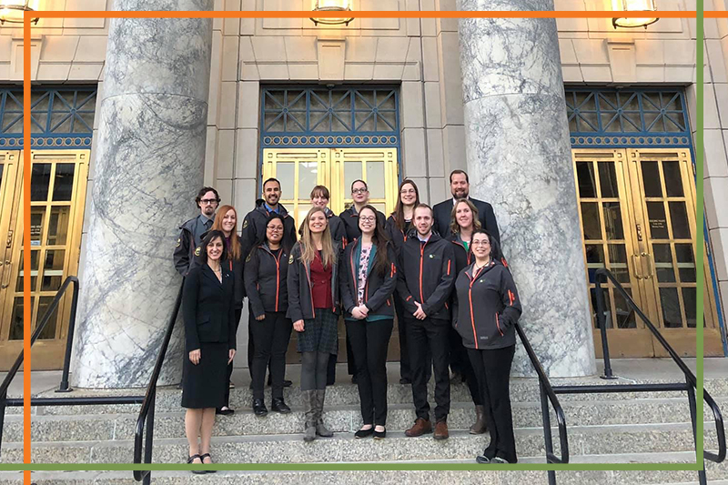 Students in gray pharmacy jackets stand with College of Pharmacy leadership on the steps of the Alaska Capitol Building during UAA ISU Capitol Fly-In Day 2019