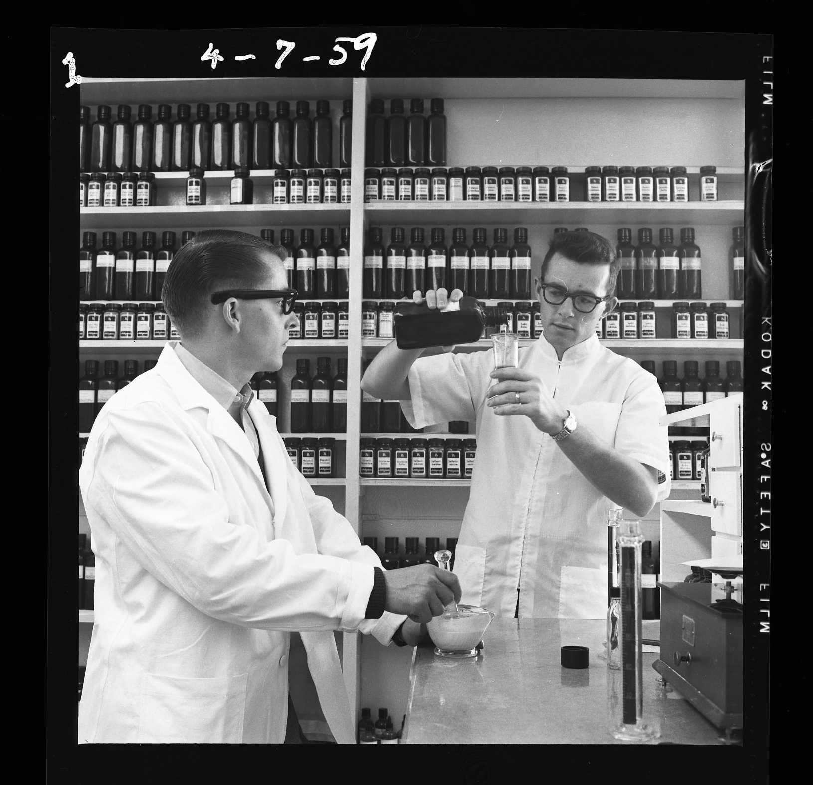 Two male pharmacists prepare a prescription in a historical photo of the College of Pharmacy