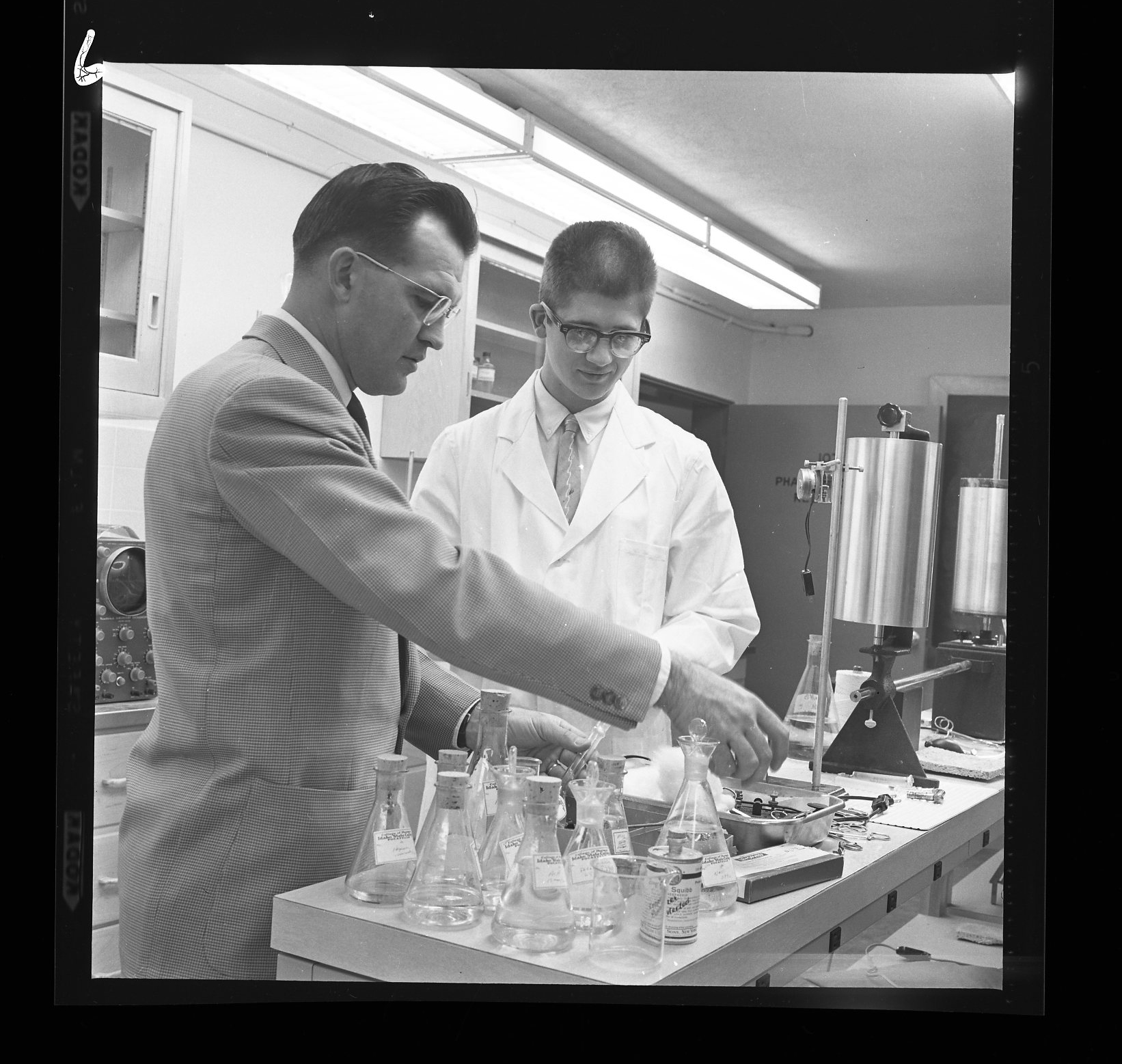 Historical photo with pharmacy dean and student in lab