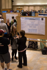 Students and faculty discussing research presentation
