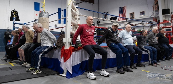 elderly men stretching against a boxing ring