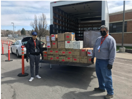 Two EHS employees loading a truck of PPE supplies to go into storage and distribution while maintaining social distancing and wearing cloth masks.