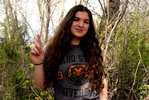 Picture of Nicole Milford in front of a tree, wearing an orange and grey Bengal tshirt.