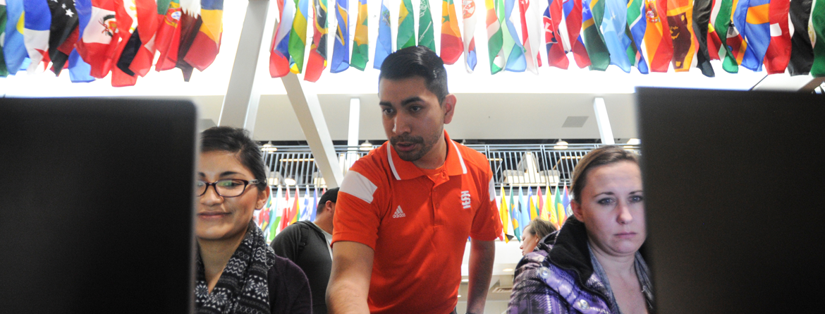 Students receiving registration help from ISU employee with international flags in the background