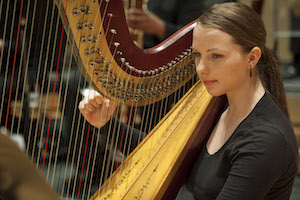 A picture of a woman playing a harp for the symphony.
