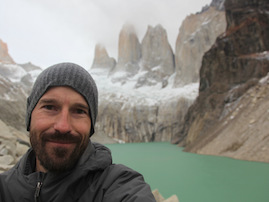 Photo of Ben Crosby with a glacial lake and mountains in the background.