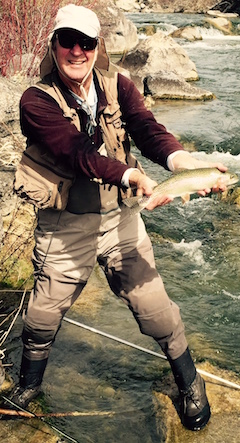 Photo of an angler in waders standing in a stream holding a big trout.