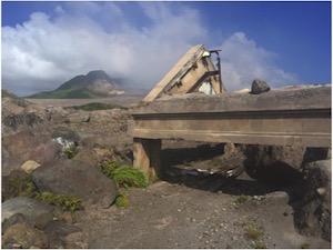 A photo of the devastation caused by the eruption of a volcano on the tiny Caribbean island of Montserrat. Shows were ash has covered the landscape and there is a bridge and road sticking out.
