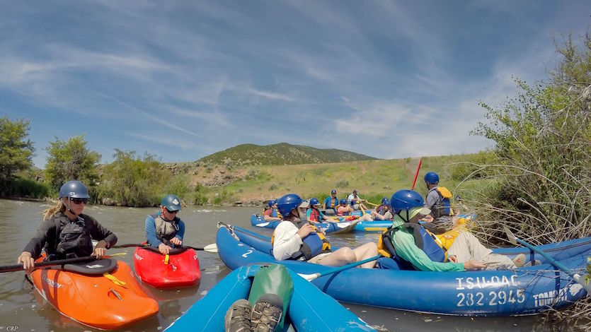 Picture of field trip participants on a river in kayaks and inflatable canoes.