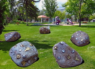 Photo of large rocks with art pieces on them.