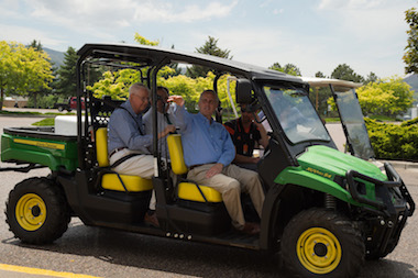 Picture of small four-wheeled John Deere vehicle with members of the Wheatley family on board, during a tour of campus.