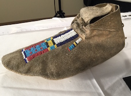 A photo of a beaded moccasin that is on display.