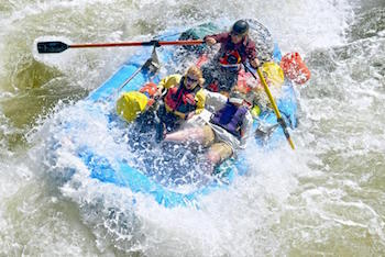 Photo of raft with three passengers splashing through whitewater rapids