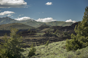 A scenic picture of the Craters of the Moon National Monument with green vegetation in the foreground, black-rock lava flows in the middle and mountains, clouds and sky in the background.