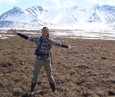 Photo of Caitlin Rushlow in Arctic with mountains in background.