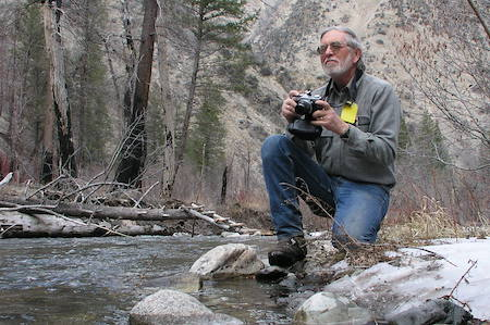 Minshall kneeling on a rock by a stream with a camera in hand.
